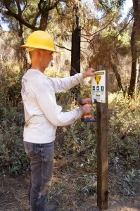 Friends of El Prieto, Banner Moffat mounts the multi-use sign to the newly installed post.